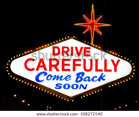 "The backside of the famous Las Vegas sign reading ""drive carefully, come back soon"""
