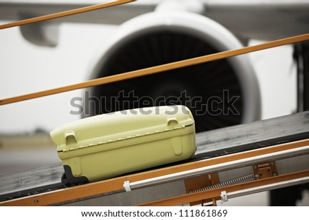 The baggage on the conveyor belt to the airplane.