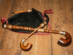 The bagpipe lies on a wooden background. Close-up.