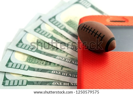 The ball for rugby or American football lies on the screen of the phone in a red case against the background of five hundred US dollars. Conceptual illustration on the theme of sports betting and #1250579575