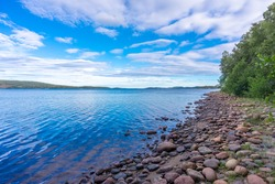 The Baltic sea coast with large granite boulders. Stony rocky shores of Sweden.  Reflections in the water. Rows of trees pines grow on the banks. Blue sky and white clouds.
