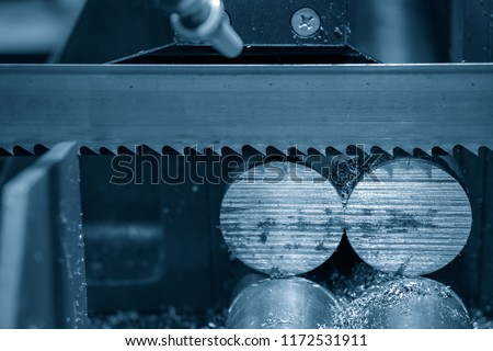 The  band saw machine cutting raw metals rods the  with the coolant fluid.The industrial sawing machine cutting the material rod.