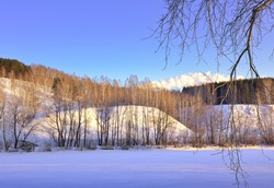 The bank of the Inya River in winter. A high slope with trees at the top among blue drifts of snow in the morning light against a clear sky. Novosibirsk, Siberia, Russia