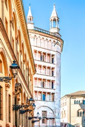 The baptistery of Parma in Piazza Duomo seen from the street with typical yellow buildings, in Parma historical center, Emilia Romagna region, Italy.