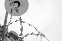 The barbed wire fence and a lantern on the background of the cloudy sky. Black-and-white photo.