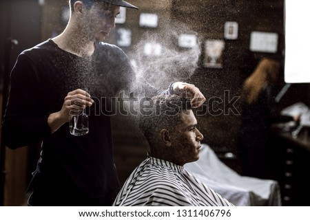 The barber dressed in a black clothes is doing the hair styling to the stylish black-haired  man sitting in the armchair in a barbershop