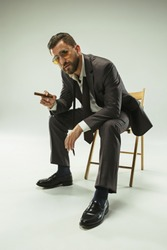 The barded man in a suit holding cigar. Stylish business man on gray studio background. Beautiful male portrait. Young emotional man. The human emotions, facial expression concept. Italian look