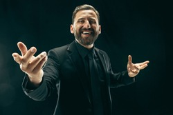 The barded man in a suit. Stylish business man on black studio background. Beautiful male portrait. Young emotional man. The human emotions, facial expression concept. Italian look.
