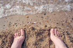 The bare feet of the man buried in the sand at the beach in summer. Relaxing on the beach. Holiday, summer and relaxation concept.
