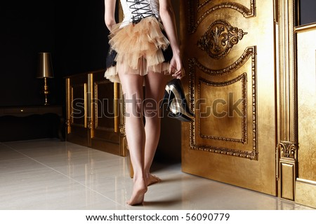 The barefoot girl in a dress leaves at a door with shoes in hands