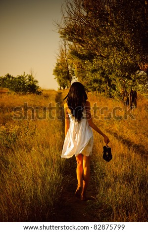 The barefoot girl in white dress with shoes in hand is on the field. Rear view