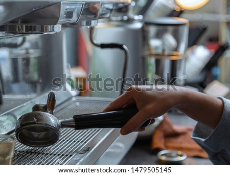 The barista is cleaning the tools. The barista is cleaning the coffee machine handle on the coffee console.