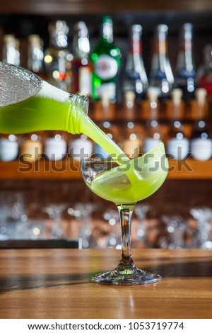 The barman in the bar pours an alcoholic cocktail into a glass with a powerful stream, not afraid to spill on the table. #1053719774