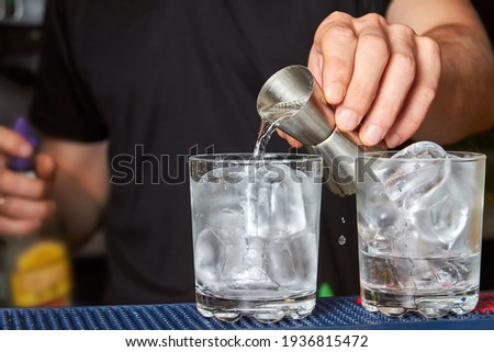 The barman pours gin into a glass with ice Foto stock ©