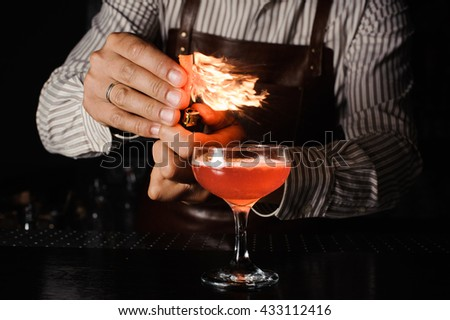 The bartender makes flame above cocktail #433112416