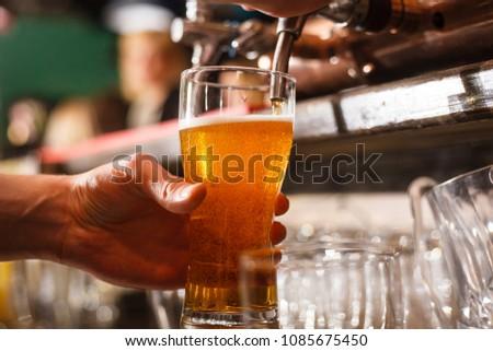 The bartender pours fresh light lager #1085675450