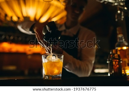 The bartender squeezes citrus juice into a cocktail Foto stock ©