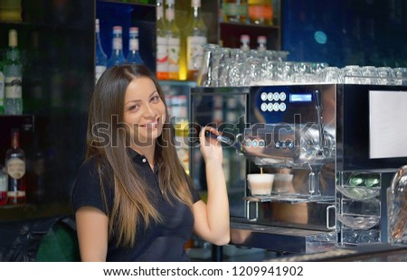 The bartender woman pours a cup of cappuccino coffee to the client in the hotel bar. Shelves with bottles of alcohol in the background. The girl is looking at the camera. The concept of service.