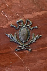The bas-relief is made of bronze on red marble.