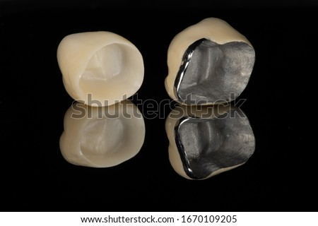 The base intaglio surface comparison between full zirconia crown and a metal ceramic/porcelain jacket dental crown with a dark background and reflection Stockfoto ©