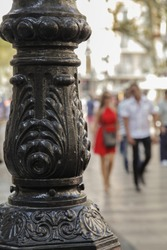 The base of the street lamp on the background of the street. Street lamp in Barcelona