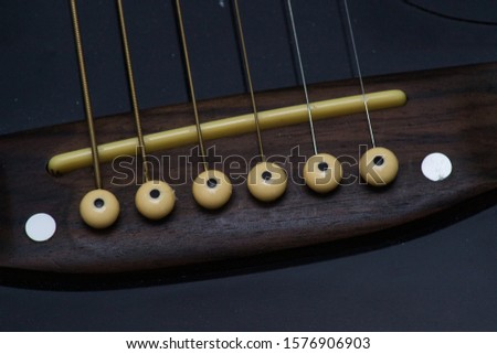 The base of the strings of a guitar