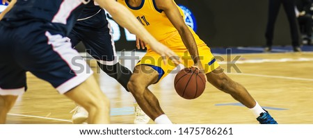 The basketball ball is on the basketball player's hand