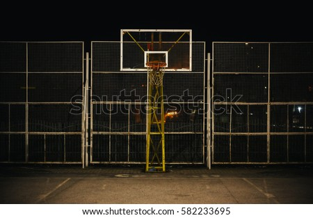 The basketball court during night, view on basketball hoop and fence. #582233695