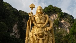 The Batu Caves Lord Murugan Statue and entrance near Kuala Lumpur Malaysia. A limestone outcrop located just north of Kuala Lumpur, Batu Caves has three main caves featuring temples and Hindu shrines.