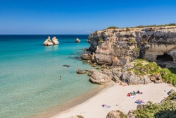 The bay of Torre dell'Orso, with its high cliffs, in Salento, Puglia, Italy. Turquoise sea and blue sky. A beach of fine white and pink sand. The stacks called the Two Sisters. Tourists sunbathe.