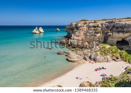 The bay of Torre dell'Orso, with its high cliffs, in Salento, Puglia, Italy. Turquoise sea and blue sky. A beach of fine white and pink sand. The stacks called the Two Sisters. Tourists sunbathe. ストックフォト ©
