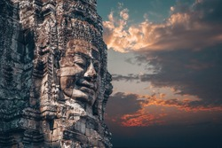The Bayon - Khmer temple at Angkor Wat in Cambodia. Popular tourist attraction. Smiling stone faces on the towers of temple. Dramatic sky