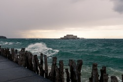 The beach and Fort National during high tide in Saint Malo (Bretagne, France) on a stormy, cloudy day in summer