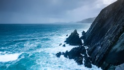 the beach and surrounding landscape at Coumeenoule harbour in the dingle peninsula in south west coast of ireland in autumn during a storm showing crashing waters onto black rock
