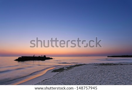 stock-photo-the-beach-at-dawn-with-fishermen-on-the-rocks-148757945.jpg