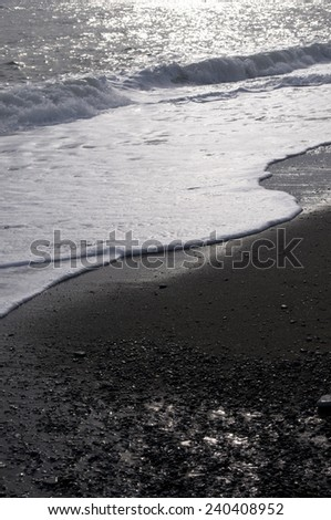 The beach fragment is presented as  self-coloured. Picture contains waves, sand and  pebble- stones.