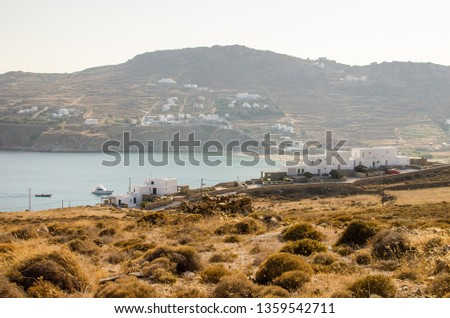 the beach of kalo livadi in mykonos, greece, with typical greek architecture and a few boats on the sea #1359542711