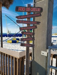 The Beach Rules sign is set against a background of white beach sand and a cloudless blue sky.