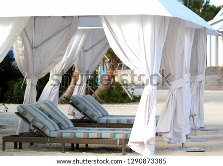 the beach with long white curtains shading classic lounge chairs with muted blue, cream and taupe stripes in Islamorada in the Florida Keys during Christmas time. #1290873385