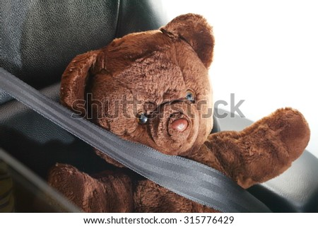 The bear doll in action of fall down the head to the car steering represent the car accident concept related idea.