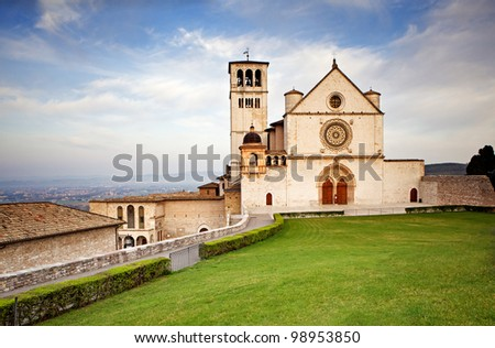 The beautiful Basilica of St. Francis of Assisi located in the town of Assisi, Italy. Photo contains a Tuscan hillside view in the background and a bright blue sky with pretty cloud formations.
