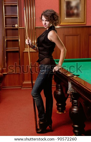 The beautiful blonde aims in the course of game at billiards