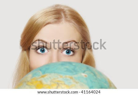 The beautiful blue-eyed girl looks out because of the globe