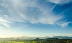 The beautiful blue sky and white clouds over rice fields and mountains, the landscape in Chiang Rai, Thailand.