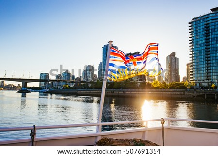 The beautiful British Columbia flag in front of downtown Vancouver at sunset.  #507691354