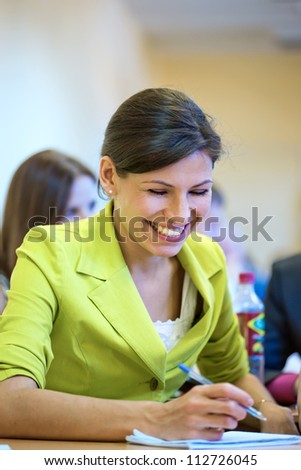 The beautiful brunette writes down and is laughs