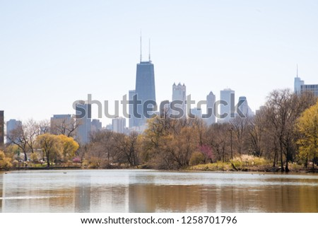 The beautiful Chicago skyline as seen from the famous Lincoln Park in autumn, with fall colors and a hazy fog in the air.