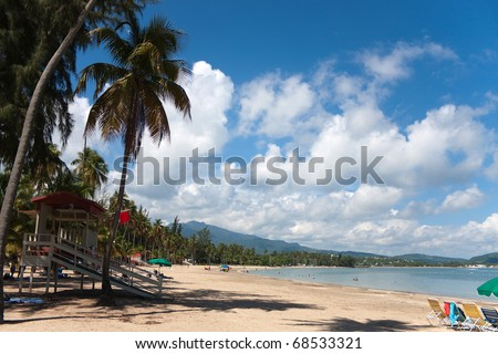 The beautiful coconut palm lined Luquillo Beach located on the large island of Puerto Rico.