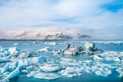 The beautiful cold winter landscape of the Jokulsarlon glacier lagoon, Iceland, in the winter with snow-capped mountain as a background.