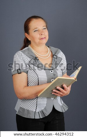 The beautiful elderly woman holds the opened book and a ball-point pen. - stock photo